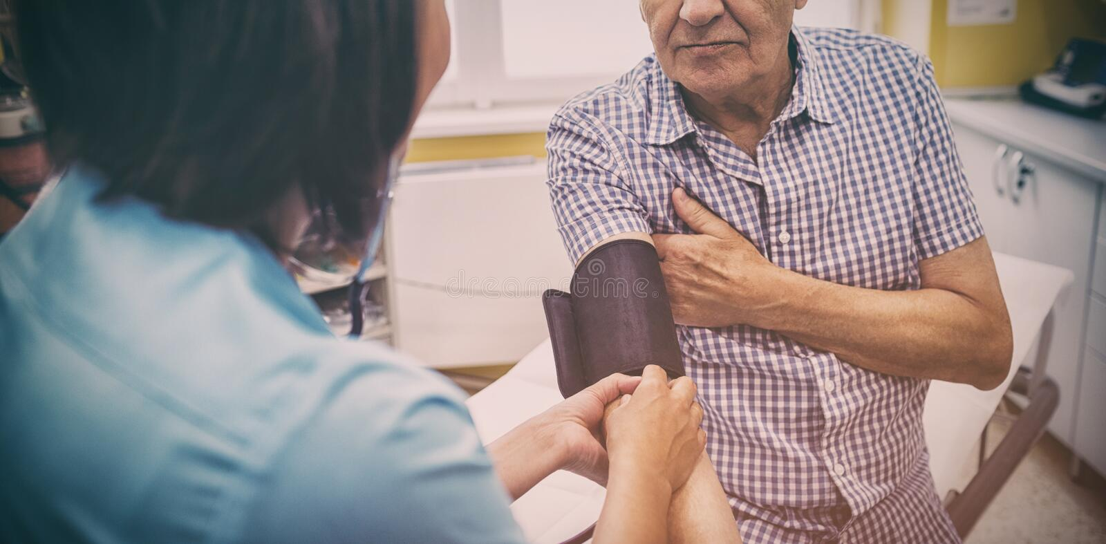 Female doctor checking blood pressure of patient stock photo