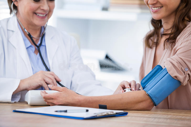 Female doctor checking blood pressure of a patient royalty free stock photography