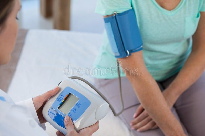 Female doctor checking blood pressure of a patient. In the hospital stock photo