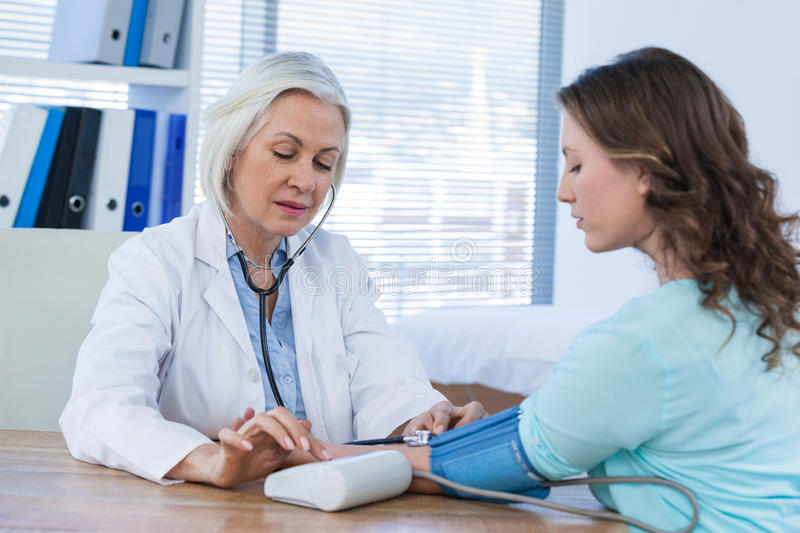 Female doctor checking blood pressure of a patient stock photos