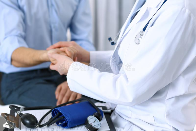 Female doctor checking blood pressure or pulse of the male patient, in hospital. Medicine and healthcare concept stock photography