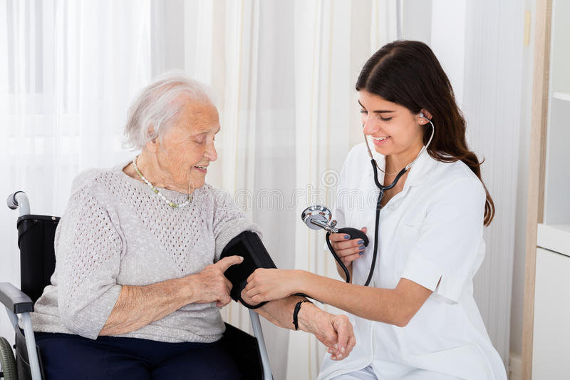 Female Doctor Checking Blood Pressure Of Senior Woman. Happy Female Doctor Measuring Senior Patient Blood Pressure With Stethoscope In Hospital stock photos