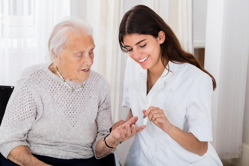 Female Doctor Checking Blood Sugar Level Of Senior Patient. Happy Female Doctor Checking Blood Sugar Level Of Senior Patient With Glucometer In Clinic royalty free stock images