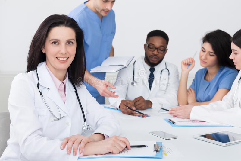 Female Doctor At Conference Looking At Camera. Female Doctor At Conference Holding Medical Report, Looking At Camera stock images