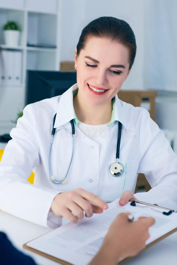 Female doctor consulting patient how to fill application form . Female doctor consulting patient how to fill application form. Physical, problem exam, er stock photos