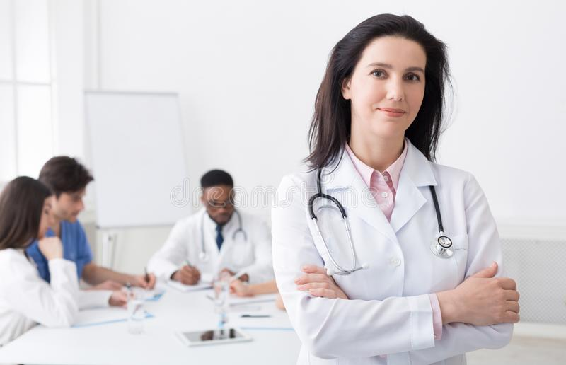 Female doctor looking at camera during meeting. Female doctor with crossed arms looking at camera during meeting in hospital royalty free stock images