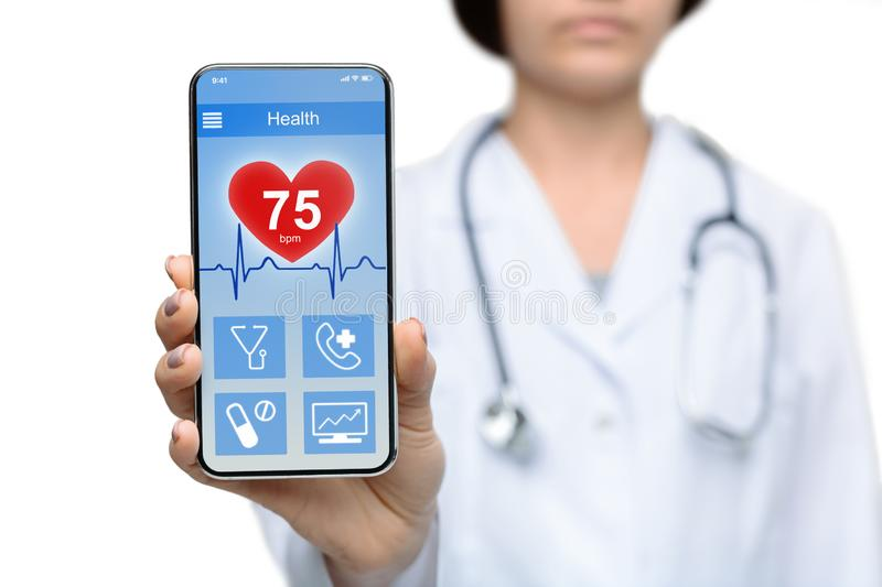 Female doctor demontrating smartphone with health rate information on screen. Medical record online. Female doctor demontrating smartphone with health rate stock photography