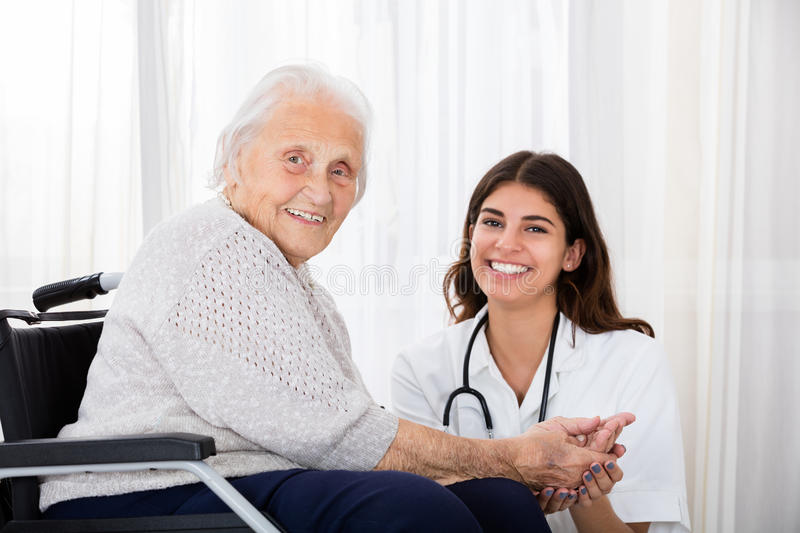 Female Doctor With Disabled Senior Patient In Hospital. Portrait Of Happy Female Doctor With Disabled Senior Patient On Wheelchair In Hospital royalty free stock photos