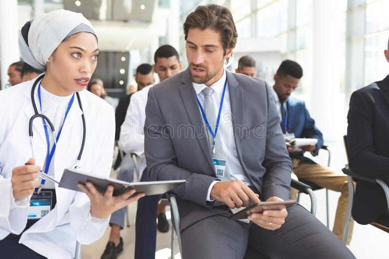 Female doctor discussing with businessman during seminar stock photo