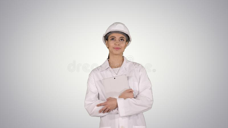 Female doctor engineer walking with digital tablet on gradient background. royalty free stock photo