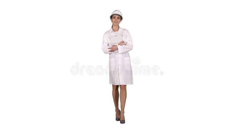 Female doctor engineer walking with digital tablet on white background. royalty free stock image