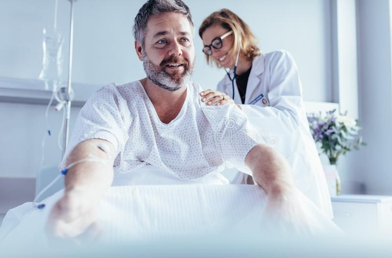 Mature man sitting in hospital bed and physician doing checkup. stock images