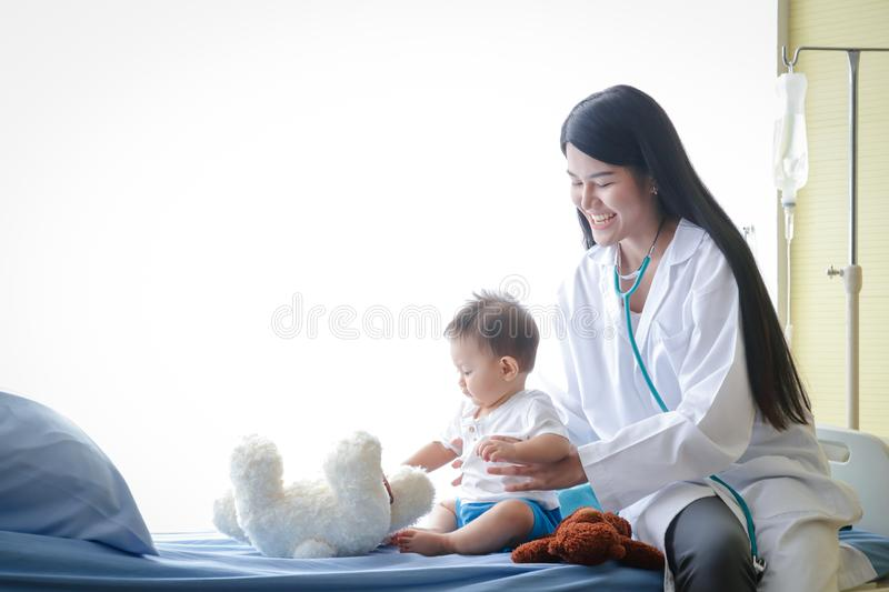 The female doctor examined the body of a young Asian patient in a bed in the clinic. royalty free stock image