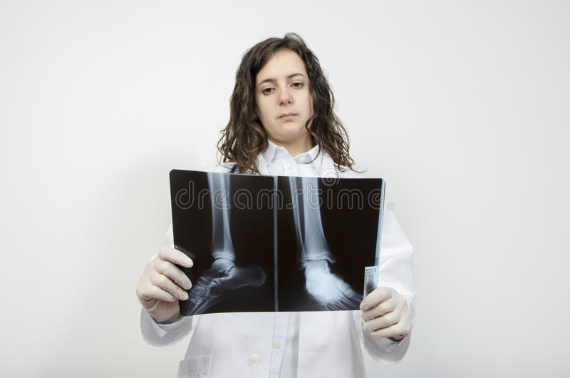 Female doctor examining accurately a foot x-ray. Confident female doctor examining accurately a foot x-ray stock images