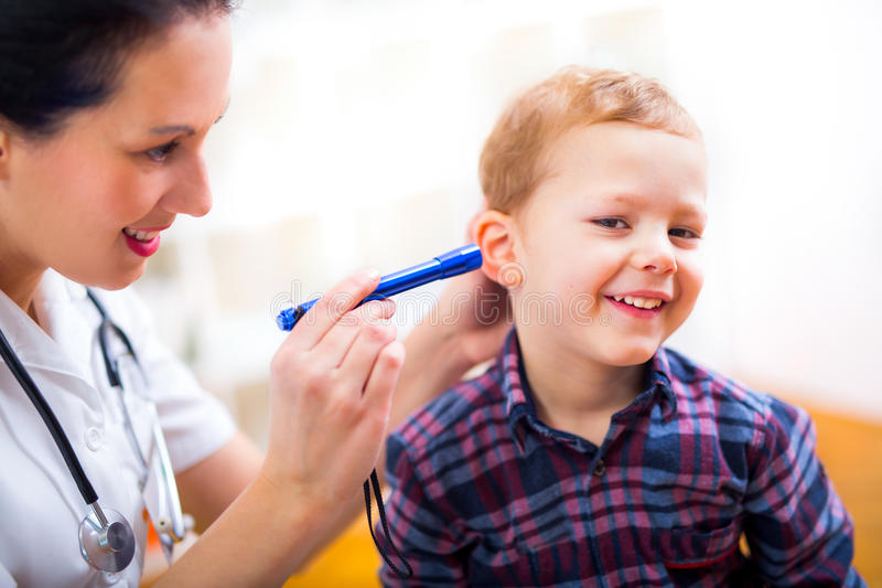 Female doctor examining little child boy. Horizontal view of boy during ear examination stock photo