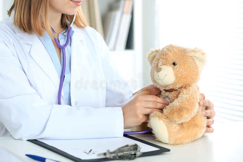 Female doctor examining a nTeddy bear patient by stethoscope. Female doctor examining a rTeddy bear patient by stethoscope. Children medical care concept stock image