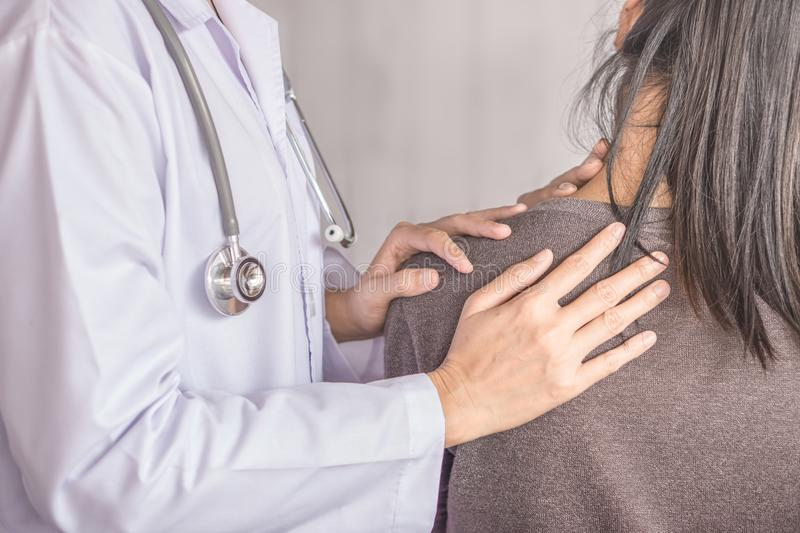 Female doctor examining a patient suffering from neck and shoulder pain stock photo