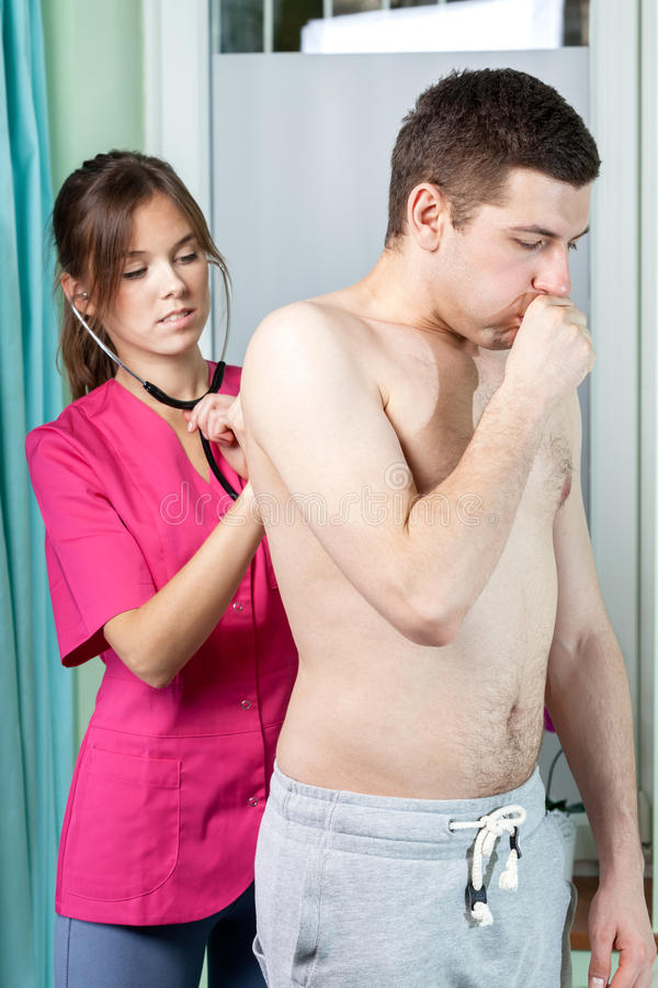 Female doctor examining young man royalty free stock images
