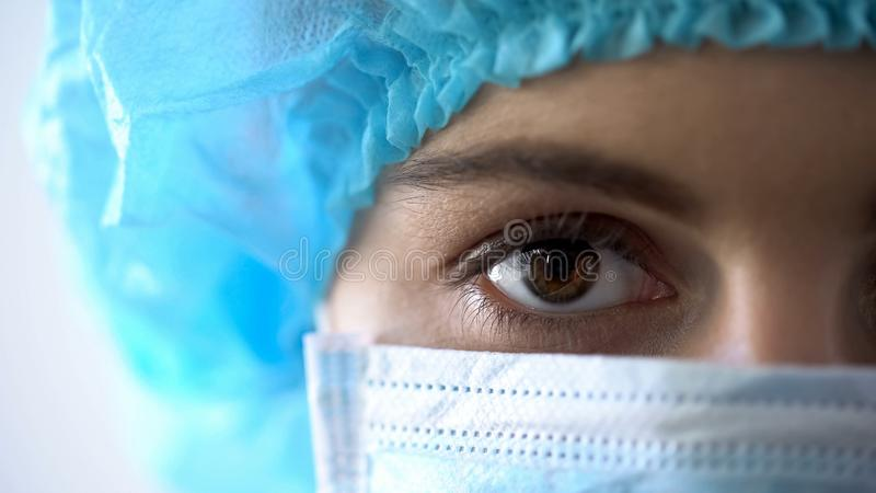 Female doctor in face mask closeup, confident look of professional doctor royalty free stock photography