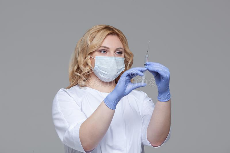 Female doctor in face mask holding syringe. Portrait of young woman doctor or nurse in protective gloves holding an stock photos