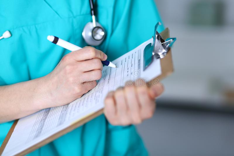 Female doctor filling up medical form on clipboard closeup. Physician finish up examining his patient in hospital an royalty free stock image