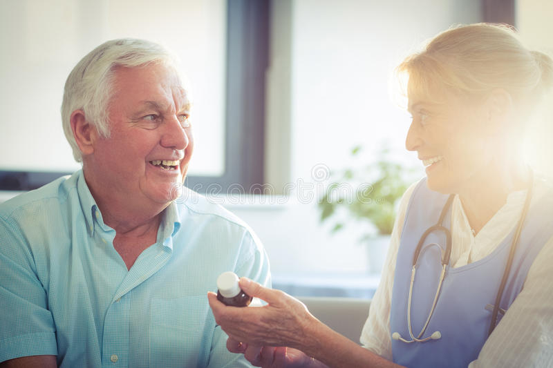 Female doctor giving medicine to senior man royalty free stock photo