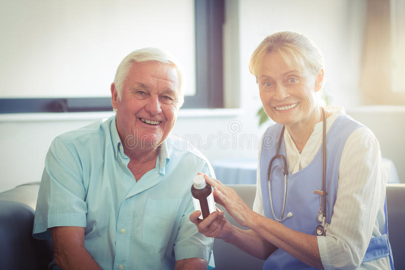 Female doctor giving medicine to senior man royalty free stock photos
