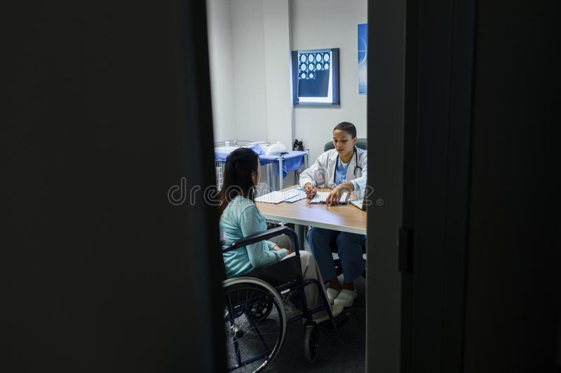 Female doctor giving prescription to disabled female patient at desk royalty free stock photos