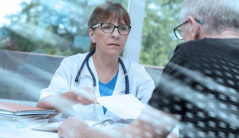 Female doctor giving prescription to her patient; multiple exposure stock photos