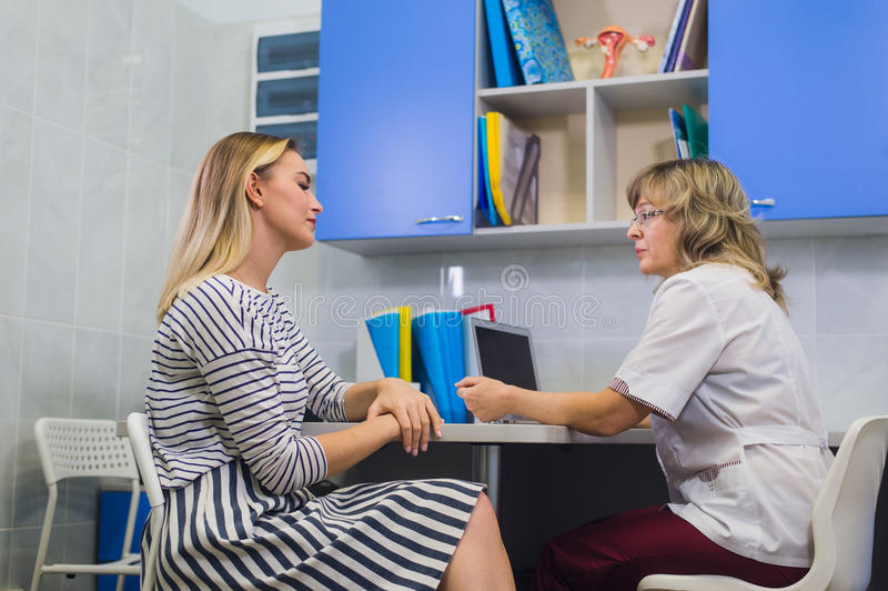 Female doctor gynecologist with patient at her office stock photo