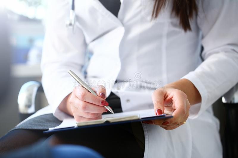 Female doctor hand hold silver pen filling royalty free stock image