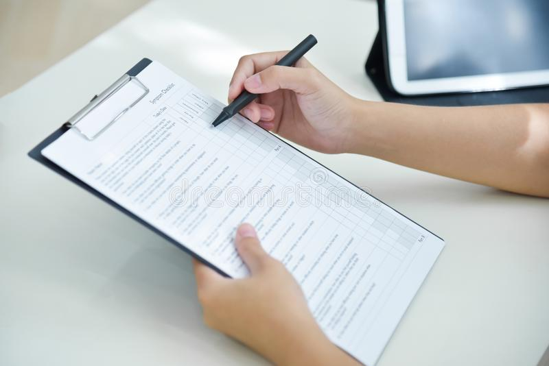 Female Doctor hands taking note on checklist. royalty free stock photo