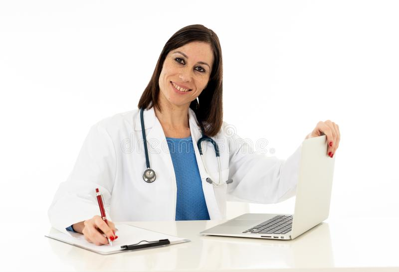 Female doctor having online consultation with patient and working on laptop isolated on white stock photo