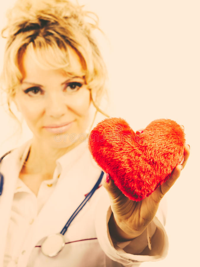Female doctor with heart. Love from working and helping people. Mid age blonde doctor in white medical apron with heart. Enjoy work concept. Filtered royalty free stock photography