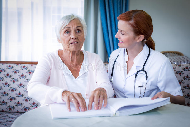 Female doctor helping a blind patient in reading the braille book. At home stock image