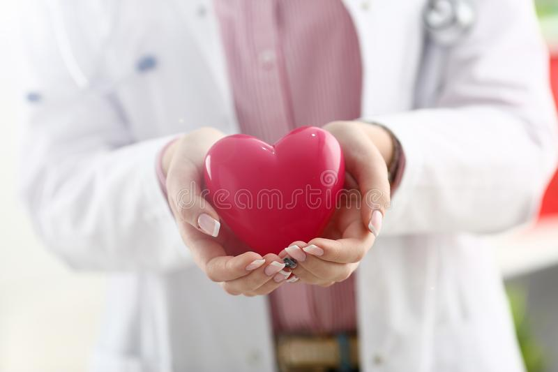 Female doctor hold in arms and cover red toy royalty free stock image