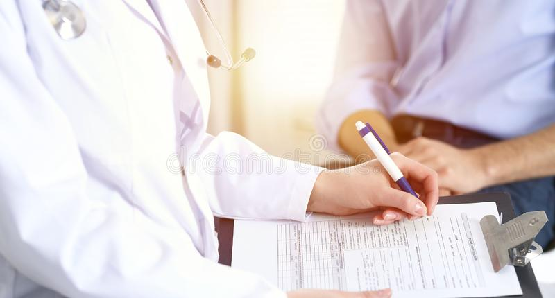 Female doctor holding application form while consulting man patient in hospital. Medicine and healthcare concept.  royalty free stock photography