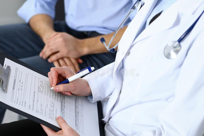 Female doctor holding application form while consulting man patient in hospital. Medicine and healthcare concept.  stock photography