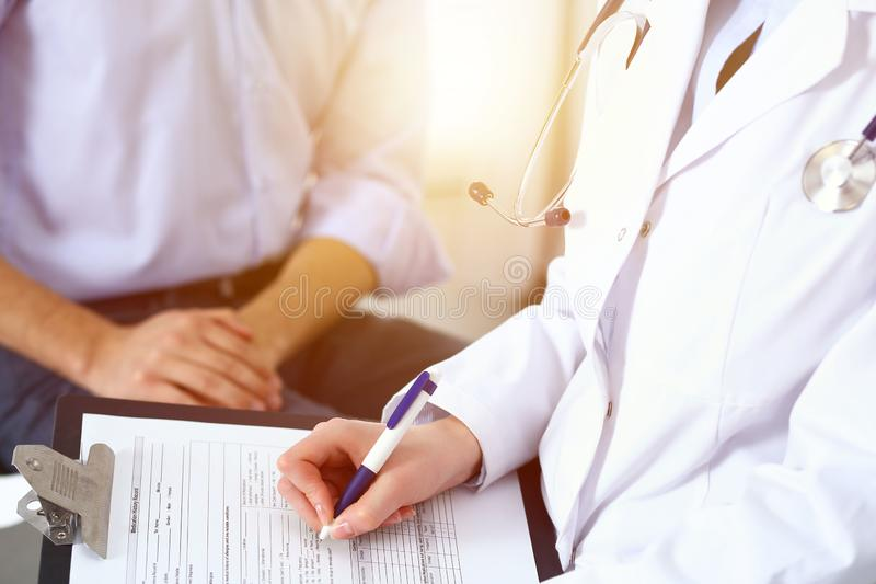 Female doctor holding application form while consulting man patient in hospital. Medicine and healthcare concept.  stock photo