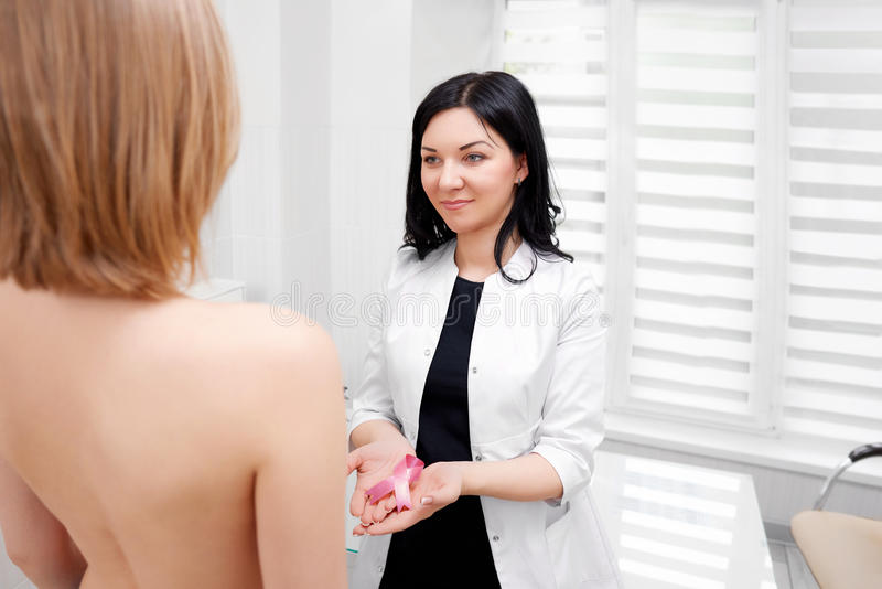 Female doctor holding breast cancer awareness pink ribbon. Cheerful young female doctor smiling at her female patient during appointment holding pink ribbon stock image