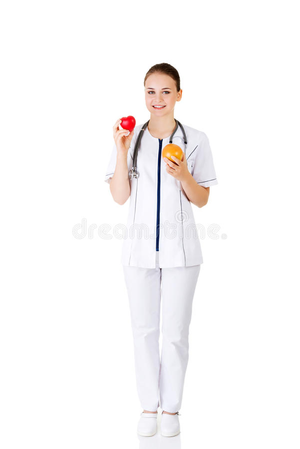 Female doctor holding healthy grapefruit and red heart. On white stock images
