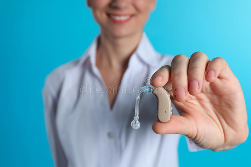 Female doctor holding hearing aid on color background, closeup. Medical object stock photography