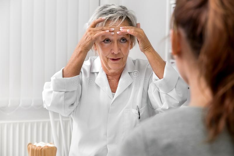 Female doctor holding her forehead, demonstration of headache or sinusitis pain stock images