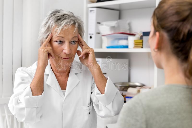 Female doctor holding her temporal, demonstration of headache or neuralgia pain royalty free stock images