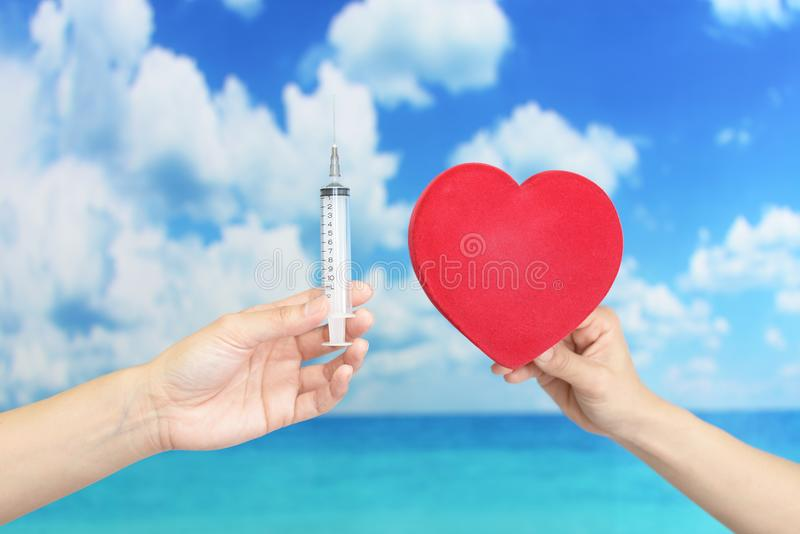 Female doctor holding injection needle. Close-up portrait of women hand with injection needle stock image
