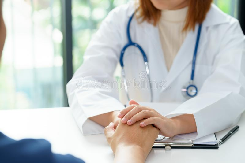 Female doctor holding patient hands for cheerful. royalty free stock photo