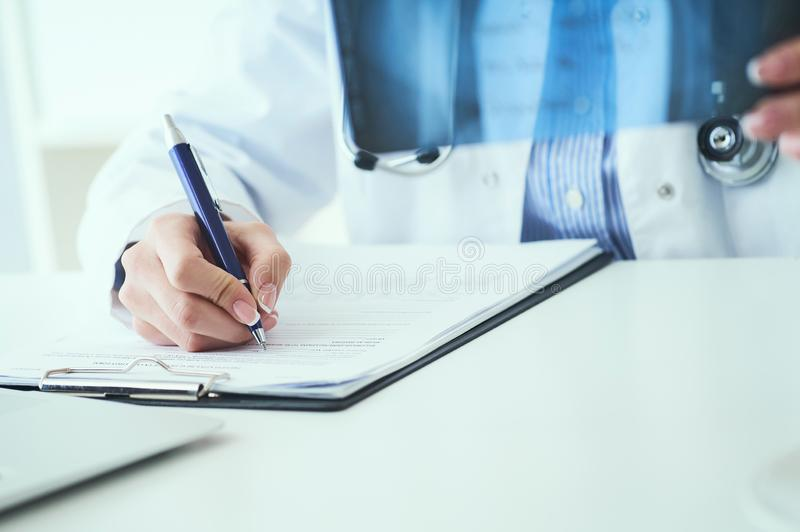 Close up of female doctor holding x-ray or roentgen image and making notes in medical form. Female doctor holding x-ray or roentgen image and making notes in stock photography