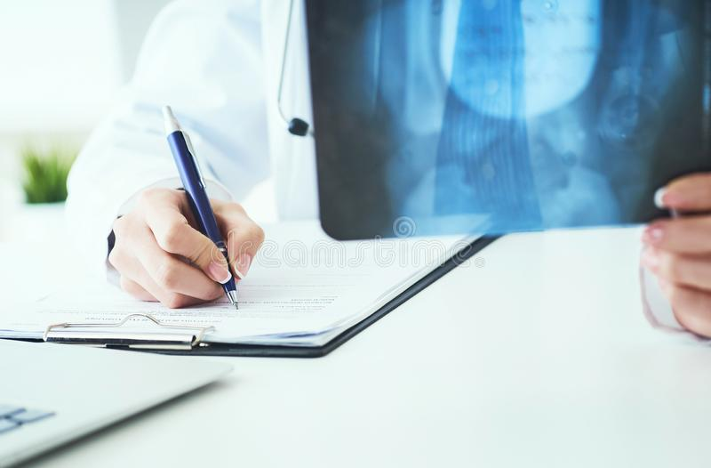 Close up of female doctor holding x-ray or roentgen image and making notes in medical form. Female doctor holding x-ray or roentgen image and making notes in royalty free stock photos