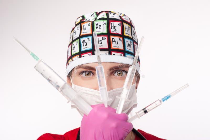 Female doctor holding several syringes in front of face. Girl injection syringe medical intervention stock image