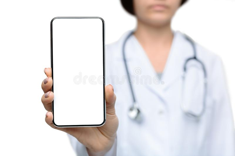 Female doctor holding smartphone with a blank screen for advertisement. Modern healthcare. Unrecognizable female doctor holding smartphone with a blank screen royalty free stock photos
